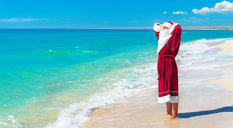 Santa Claus relaxing at sandy sea beach - Christmas concept